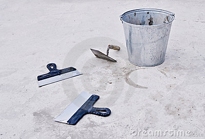 Metal bucket with cement and spatulas