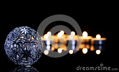 Metal christmas ball in front of tea candles