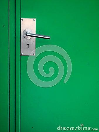Metal door handle on green