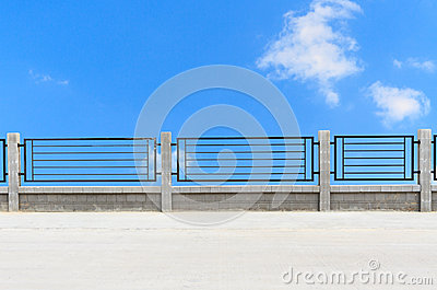Metal fences on cement road with clouds