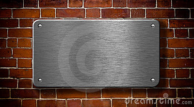 Metal plate with rivets on brick background