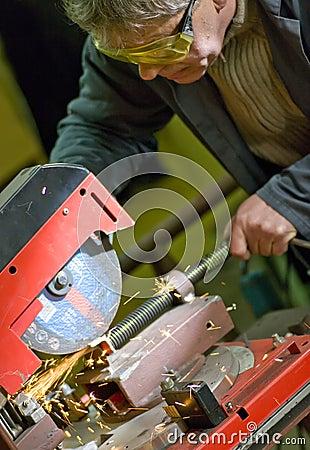 Metalworker cutting metal