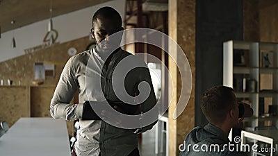 Metragem acelerada O homem de negócio afro-americano concentrado jovens está andando com uma tabuleta em na sua mão e datilografi video estoque