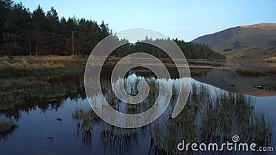 Metragem bonita do lago imóvel e montanhas contra o céu filme