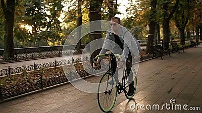 Metragem dianteira de um homem de sorriso novo nos óculos de sol que dão um ciclo uma bicicleta no parque ou no bulevar da manhã  vídeos de arquivo