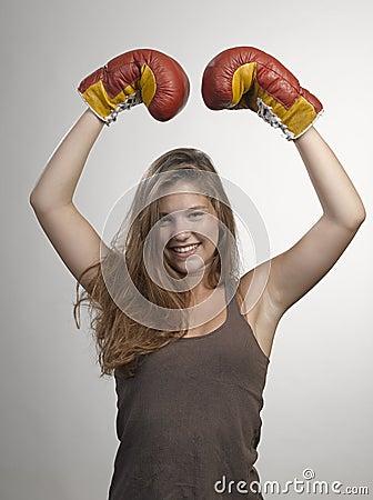 Metta in mostra i guantoni da pugile della giovane donna, fronte dello sho dello studio della ragazza di forma fisica