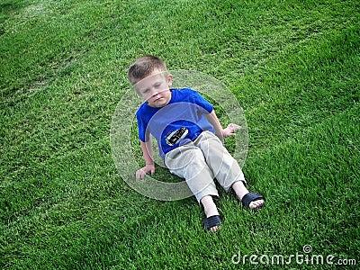 Miúdo mal-humorado na grama