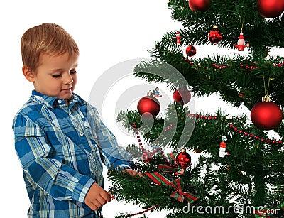 Miúdo que decora a árvore de Natal