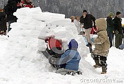 Miúdos que constroem um igloo (casa da neve)