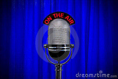 Microphone on stage with spotlight on blue curtain