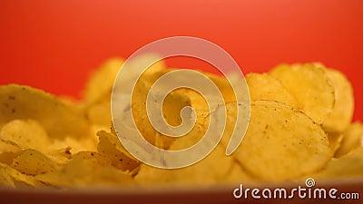 Microplaquetas friáveis douradas close up, comida lixo com realçadores do sabor, riscos para a saúde filme