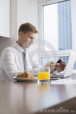 Mid adult businessman using cell phone with laptop on breakfast table