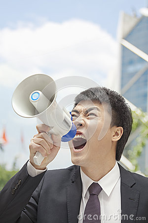 Mid Adult Businessman yelling into a megaphone, outdoors, Beijing, China