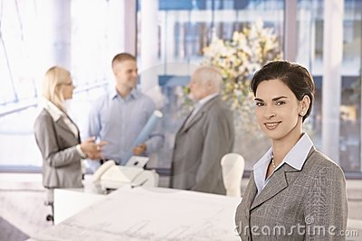 Mid-adult businesswoman in office with colleagues