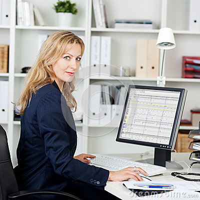 Mid Adult Businesswoman Using Computer At Desk