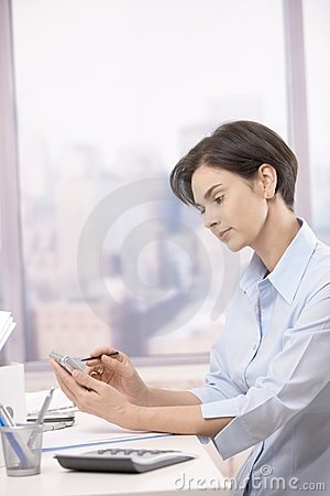 Mid-adult businesswoman using pda in office