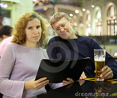 Mid adult couple reading menu card