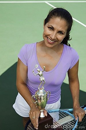 Mid-adult female tennis player holding trophy