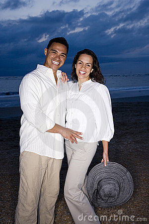 Mid-adult Hispanic couple smiling on beach at dawn