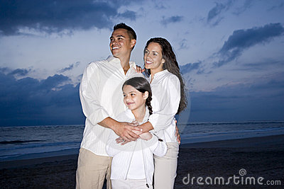 Mid-adult Hispanic family smiling on beach at dawn