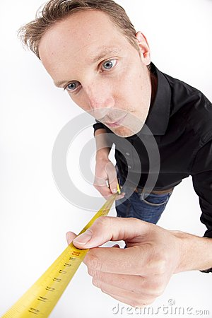 Mid adult man holding tape measure