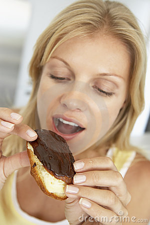 Mid Adult Woman Eating A Chocolate Eclair