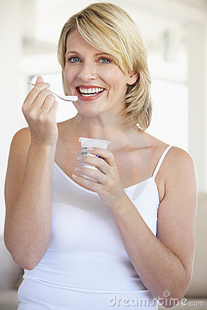 Free Mid Adult Woman Eating Yogurt Royalty Free Stock Photo - 7874735
