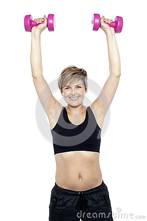 Mid adult woman holding dumbbells over head