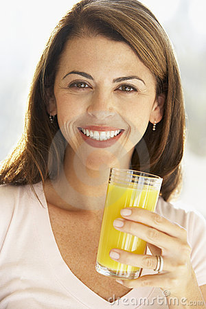 Mid Adult Woman Holding A Glass Of Orange Juice