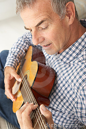 Mid age man playing acoustic guitar