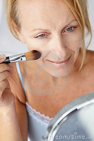 Mid age woman applying make-up