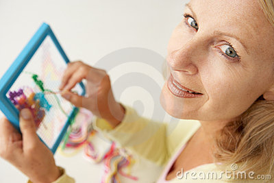 Mid age woman doing cross stitch