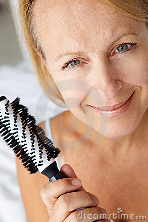 Mid age women looking at camera with a hairbrush