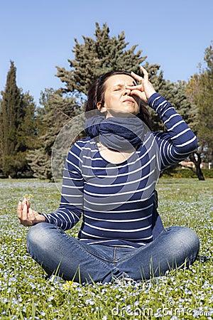Mid aged woman doing yoga pranajama exercises outside