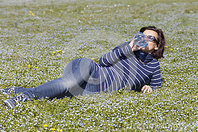 Mid aged woman relaxing and drinking water on grass