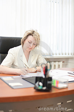 Mid-life business woman sign document