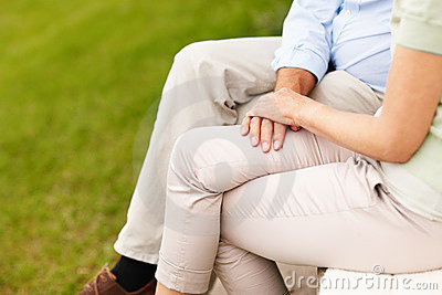 Mid section of a couple sitting on a bench