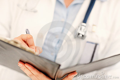 Mid section of a doctor making a note in a file
