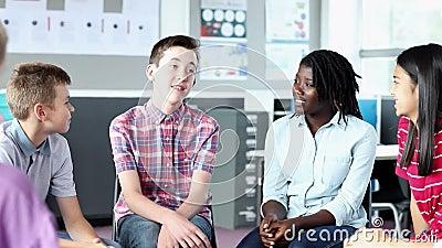 Middelbare schoolstudenten die informele bespreking met vrouwelijke leraar in klaslokaal hebben stock videobeelden