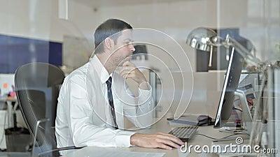 Middelouderdomse zakenman die aan de Computer van het Bureau denkt en werkt stock videobeelden
