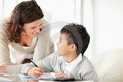 Midden oude dame die haar zoon helpt om thuiswerk te doen