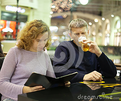 Middle age couple reading menu card