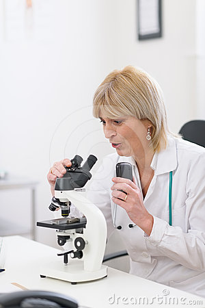 Middle age doctor woman looking in microscope