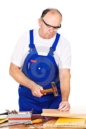 Middle age worker hammering nails in board
