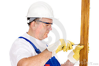 Middle age worker screwing nail in board