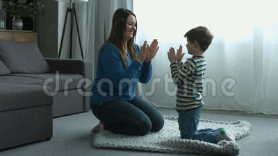 Happy boy and mother playing patty cake at home stock video