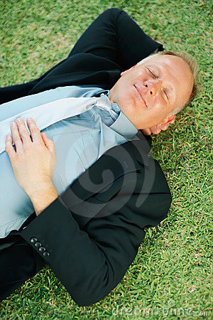 Middle aged business man sleeping on the grass