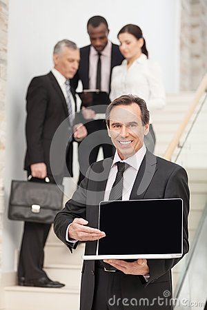 Middle aged business man using laptop with executives in the bac