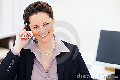 Middle aged business woman using a headset at work