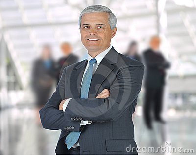 Middle aged Businessman arms crossed in Lobby